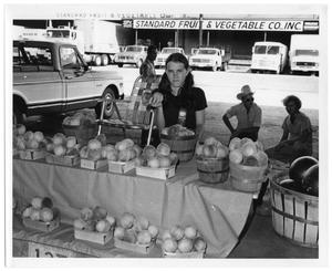 Primary view of object titled '[Girl in Front of Standard Fruits & Vegetables Co., Inc.]'.