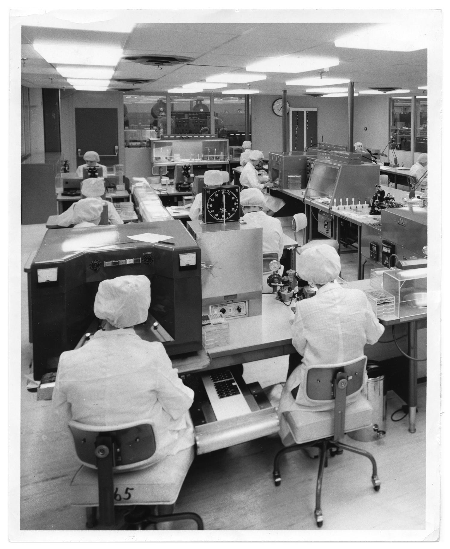 Texas Instruments, Photograph of several employees in a laboratory at Texas Instruments. The employees are all sitting down at tables with laboratory equipment; they are wearing lab coats and hair coverings.,