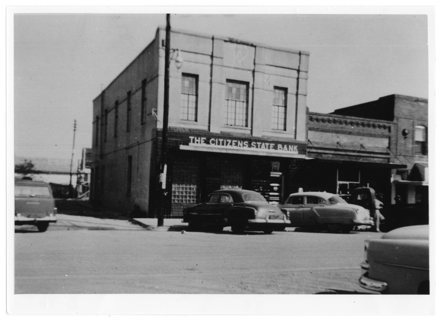 """Citizens State Bank, 1954, Photograph of an exterior view of Citizens State Bank on Main Street in Richardson, Texas. The bank is a brick building with a sign that says """"The Citizens State Bank"""" over an awning, and a Freemasonry symbol at the top. Other buildings are connected to the right of it. Cars are parked outside the building.,"""