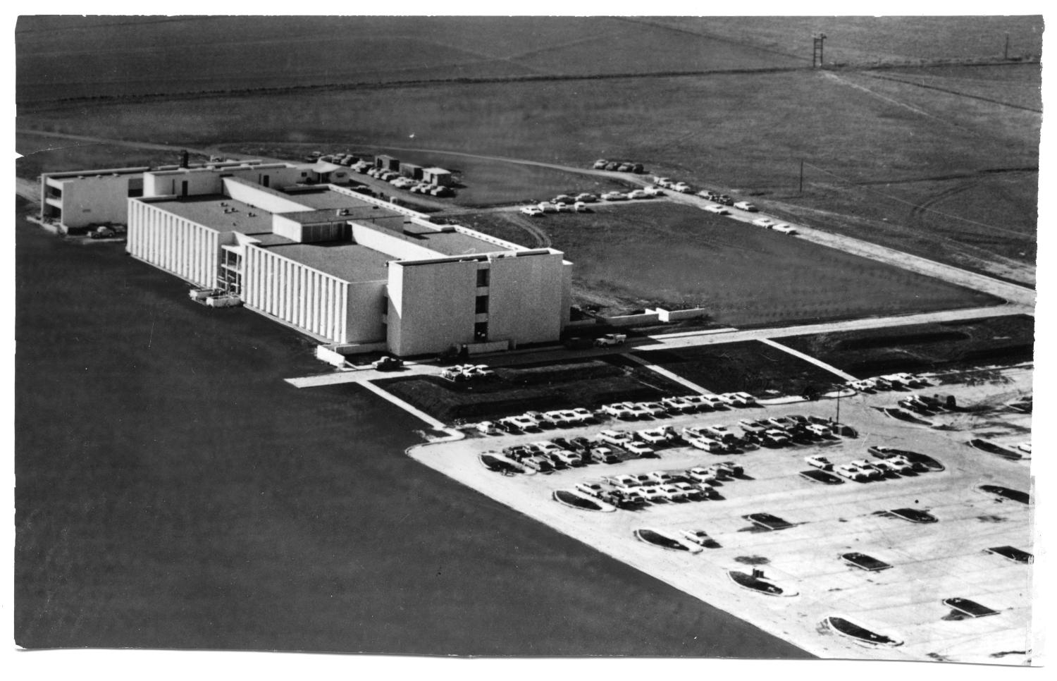 Southwest Center for Advanced Studies (University of Texas - Dallas in Richardson), Photograph of an aerial view of the Southwest Center for Advanced Studies, now known as University of Texas - Dallas. A parking lot with cars is located to the right of the building. In the background, there are cards parked on the sides of roads.,