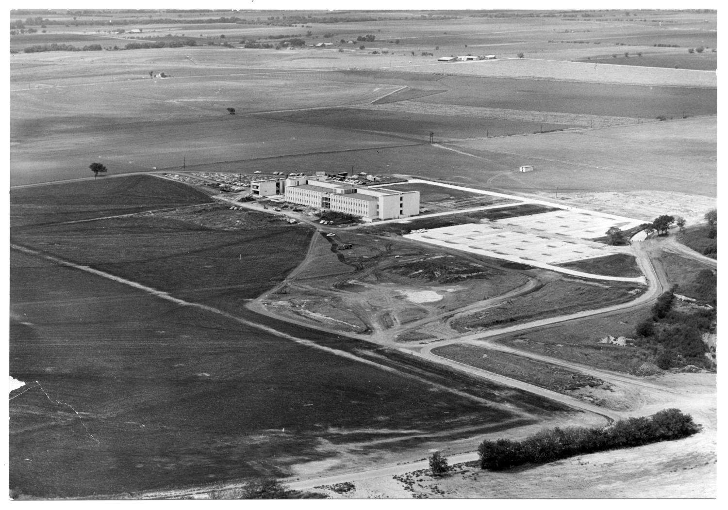 Southwest Center for Advanced Studies, Photograph of an aerial view of Southwest Center for Advanced Studies, now known as University of Texas - Dallas. There is a parking lot on the left side of the building. The building is surrounded by roads and open fields.,