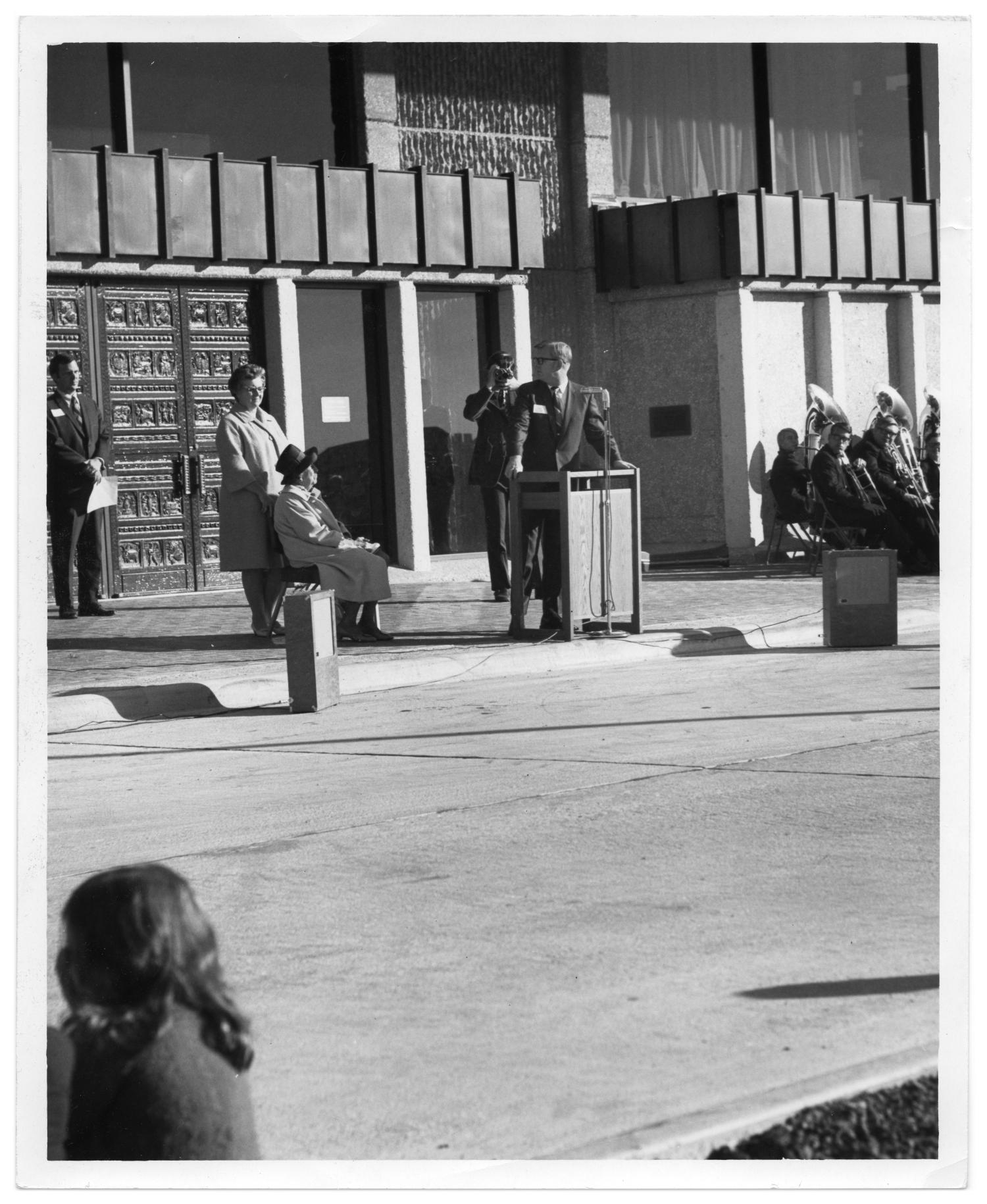 Richardson Public Library, Photograph of a group of people at the opening of the new, four-story Richardson Public Library on 900 Civic Center Drive in Richardson, Texas. One man is standing at a podium, one man is sitting to his left, and one woman is standing behind the seated man. They are identified as Mayor Ray Noah, James V. Kincaid (Chairman of Library Board), and Marguerite Anderson (librarian). To the far right, there are members of a band sitting. In the background, there is a view of the library.,