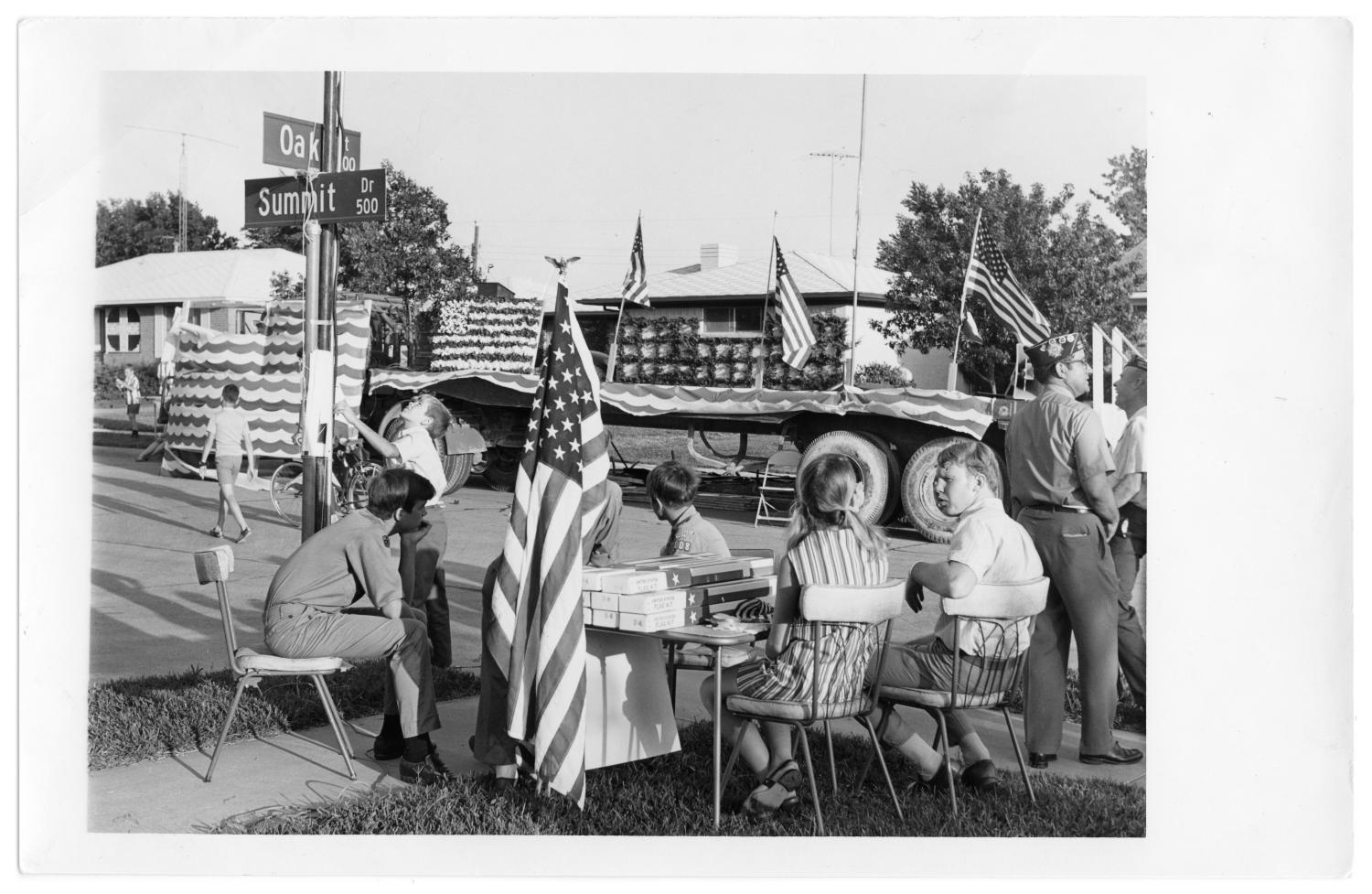 """Fourth of July Parade, Photograph of Independence Day parade at the corner of Oak Street and Summit Drive in Richardson, Texas. A semi truck parade float is decorated with flags, streamers, and paper. In the foreground, there are people seated and standing near a table with boxed United States flags on it. A flag is set up at the table. To the left, there is a street sign with """"Oak Street"""" and """"Summit Drive."""","""