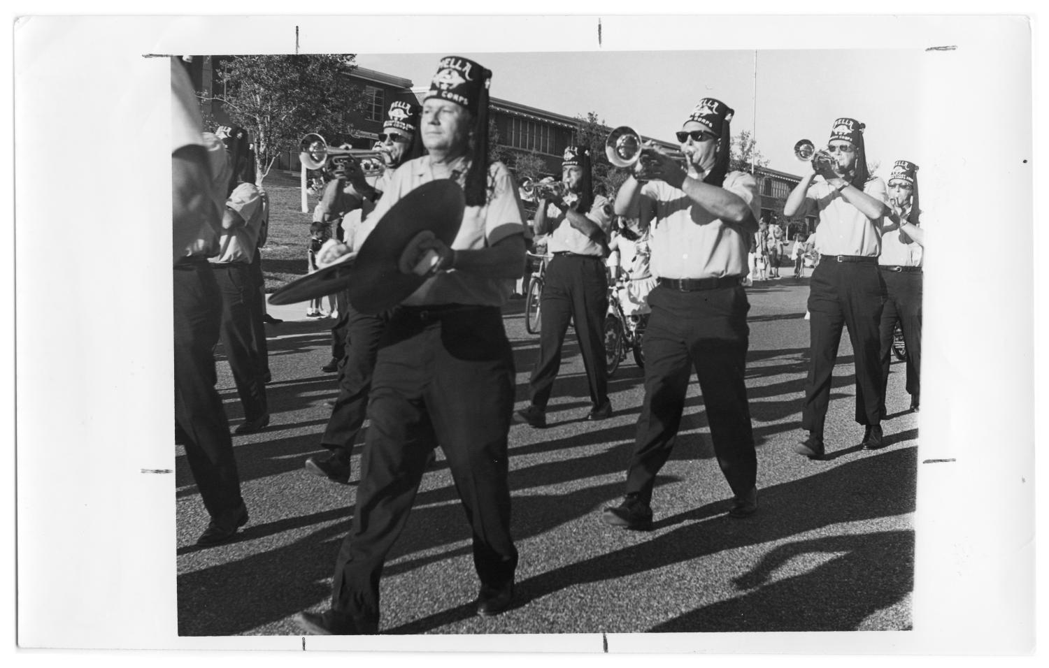Fourth of July Parade, Photograph of men in a marching band at the Independence Day parade, on Beltline Road in front of Richardson High School. The men are wearing Shriners fezzes. One man is holding a pair of symbols, and the men behind him are playing trumpets.,