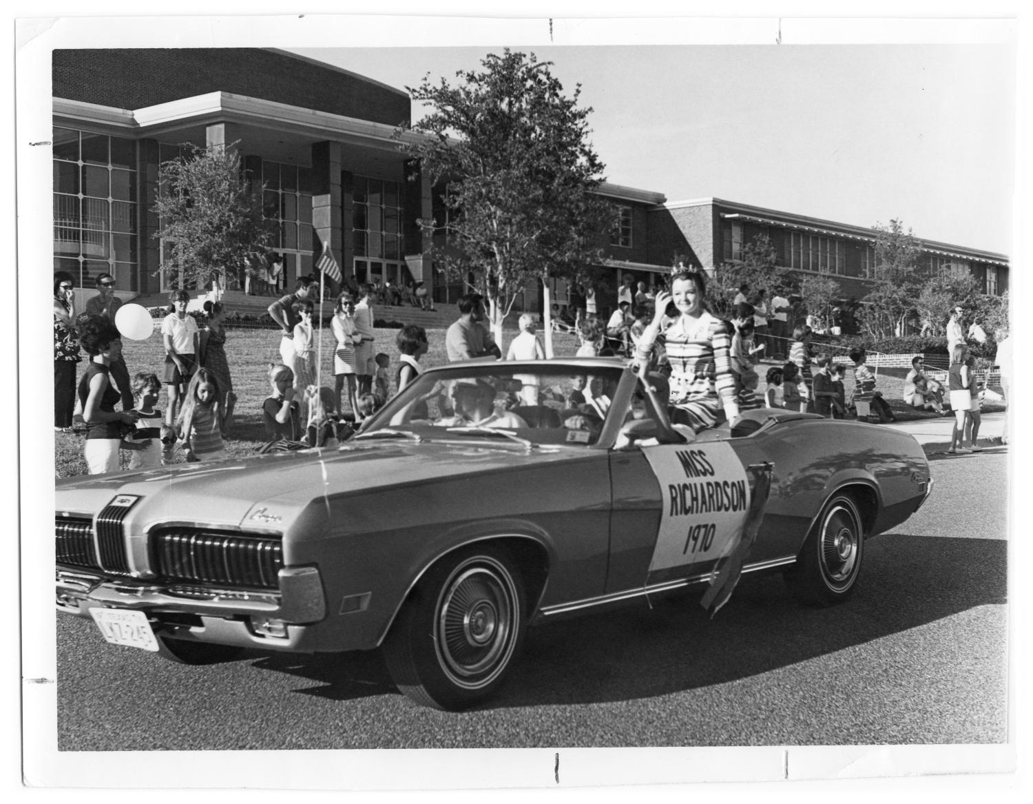 """Fourth of July Parade, Photograph of a young woman sitting on the back of a convertible car in a parade on Beltline Road, in front of Richardson High School. She is wearing a striped dress and a crown. A sign on the side of the cars says """"Miss Richardson 1970."""" In the background, there is a group of people on the yard of the high school.,"""
