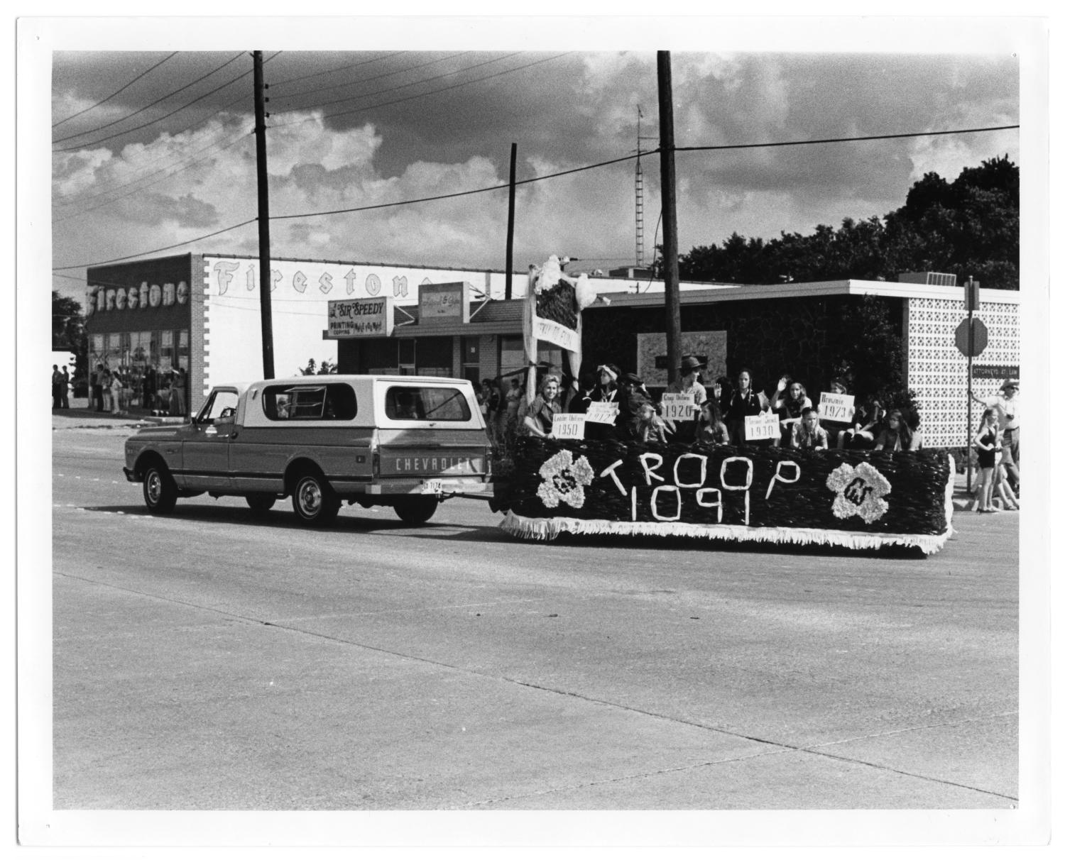 """Richardson Centennial Parade, Photograph of the Girl Scout Troop 1091 parade float, at the intersection of Main Street and Greenville Avenue in Richardson, Texas. The float is attached to the back of a Chevrolet truck. Girls on the float are wearing uniforms and holding signs illustrating what year their uniform was worn. A sign on the front of the float made of streamers has the Girl Scout logo and """"Troop 1091"""" on the front. In the background, there are people watching in front of businesses; one building on the left says """"Firestone"""" on the front and side.,"""
