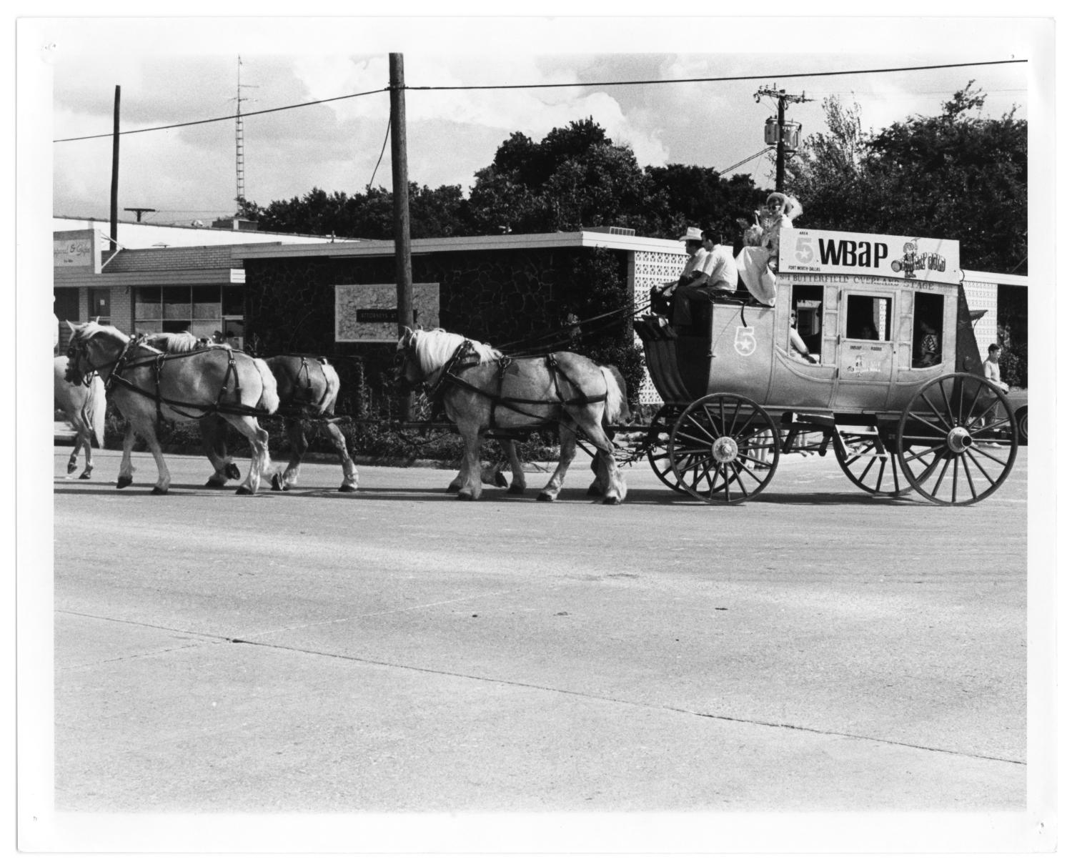 """Richardson Centennial Parade, Photograph of a stagecoach wagon float in the centennial parade, at the intersection of Main Street and Greenville Avenue in Richardson, Texas. The wagon is pulled by four matching horses, and two men and two women are riding on it. A sign on the side of the wagon says """"5 WBAP Country Gold;"""" the side of the wagon says """"Butterfield Cleveland Stage."""" In the background, there are businesses.,"""