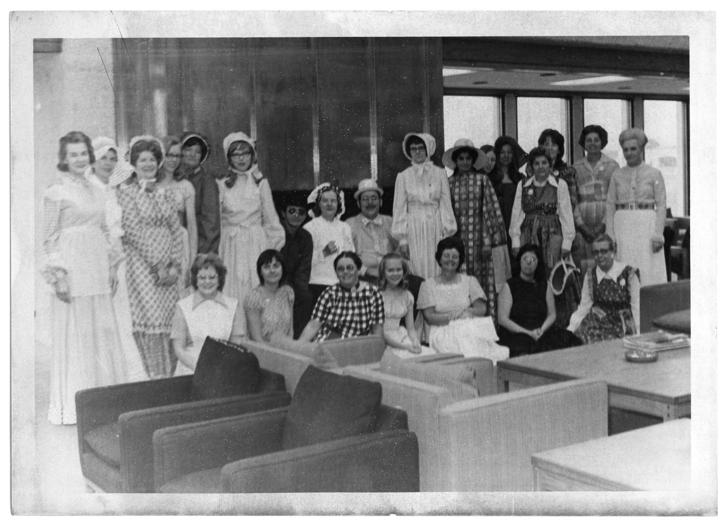 Richardson Public Library - Centennial Costumes, Photograph of twenty-three women and two men posing in front of a copper-clad fireplace at Richardson Public Library. They are wearing costumes in celebration for the centennial of Richardson, Texas. Seven people are identified as Gerrie Mason (left), Bertha (Bird) ONeal (fourth from right), Tony Rampino (back row, center), Louise Frederick (back row, center), Paul Smith (back row, center), Marita Mangan (fourth from left), and Charlie Unk (far right). In the foreground, there is a group of chairs.,