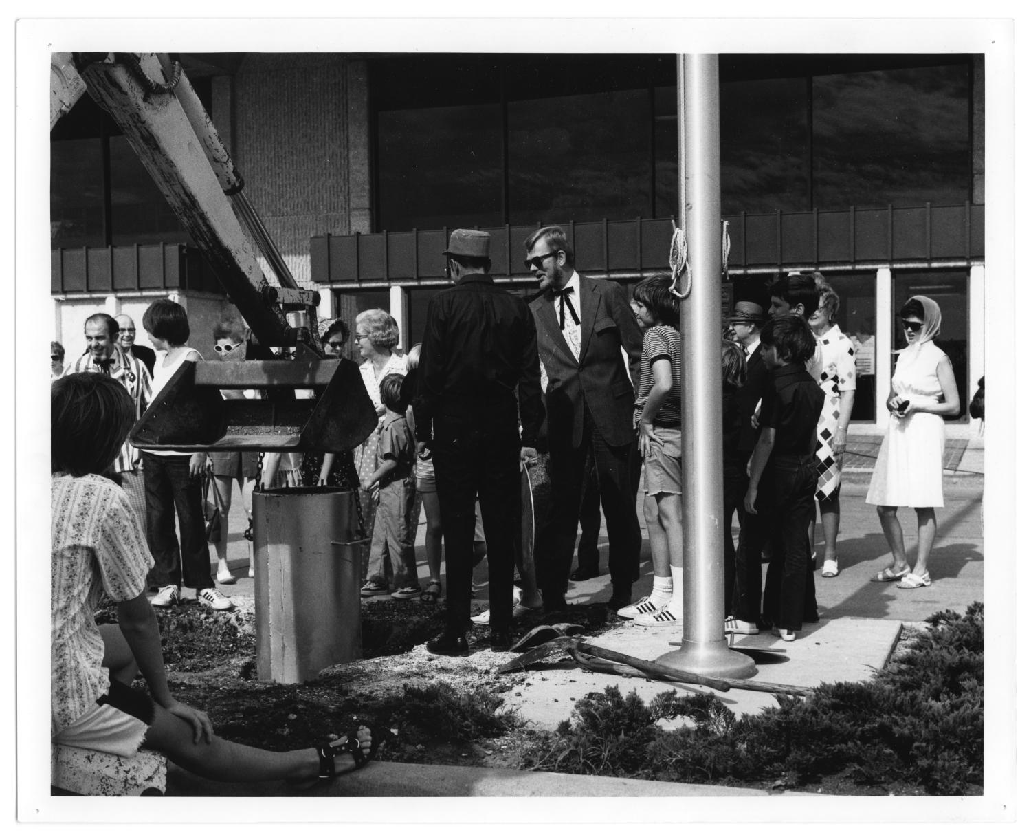 Richardson Public Library - Time Capsule, Photograph of a time capsule lowered into the ground at a centennial celebration for Richardson, Texas. A group of children, women, and men are gathered around the capsule. A piece of construction machinery is lowering it. In the background, there is a building identified as Richardson Public Library.,