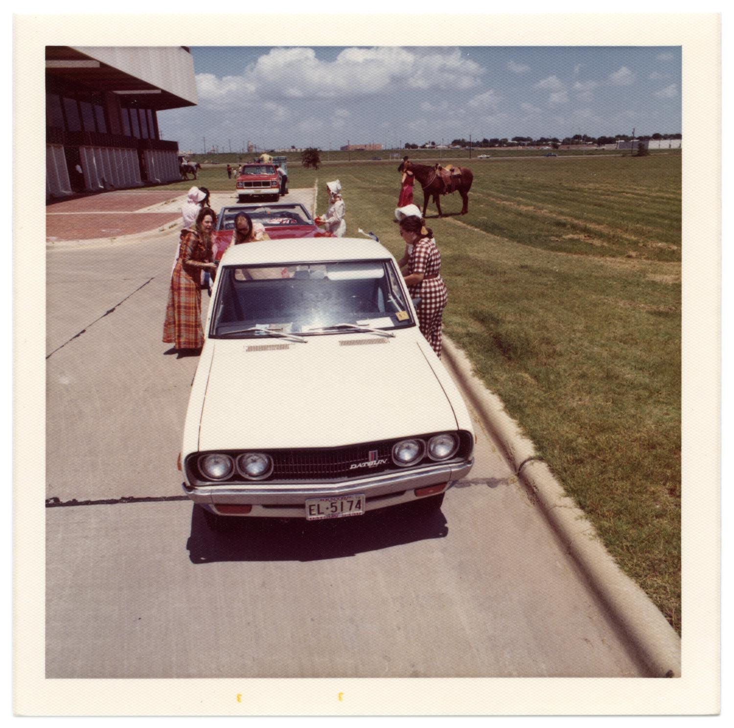 Richardson Centennial Parade, Photograph of cars parked in a line waiting to participate in the Centennial parade. A group of women wearing costumes are gathered around the back of a white Datsun car. Behind the white car, there are women dressed in costume gathered around a red convertible. In the background, there is a woman and horse on a grass lot, and people beside a red truck.,