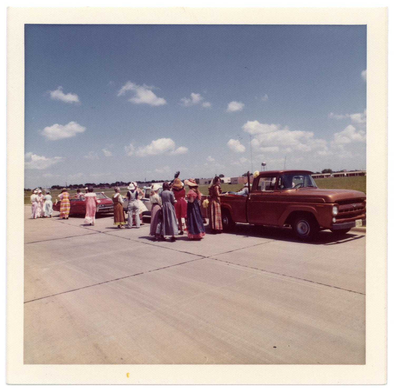 Richardson Centennial Parade, Photograph of a group of people wearing costumes and waiting to participate in the Centennial parade. There are two trucks and one convertible car parked behind them. In the background, there is a grassy field.,