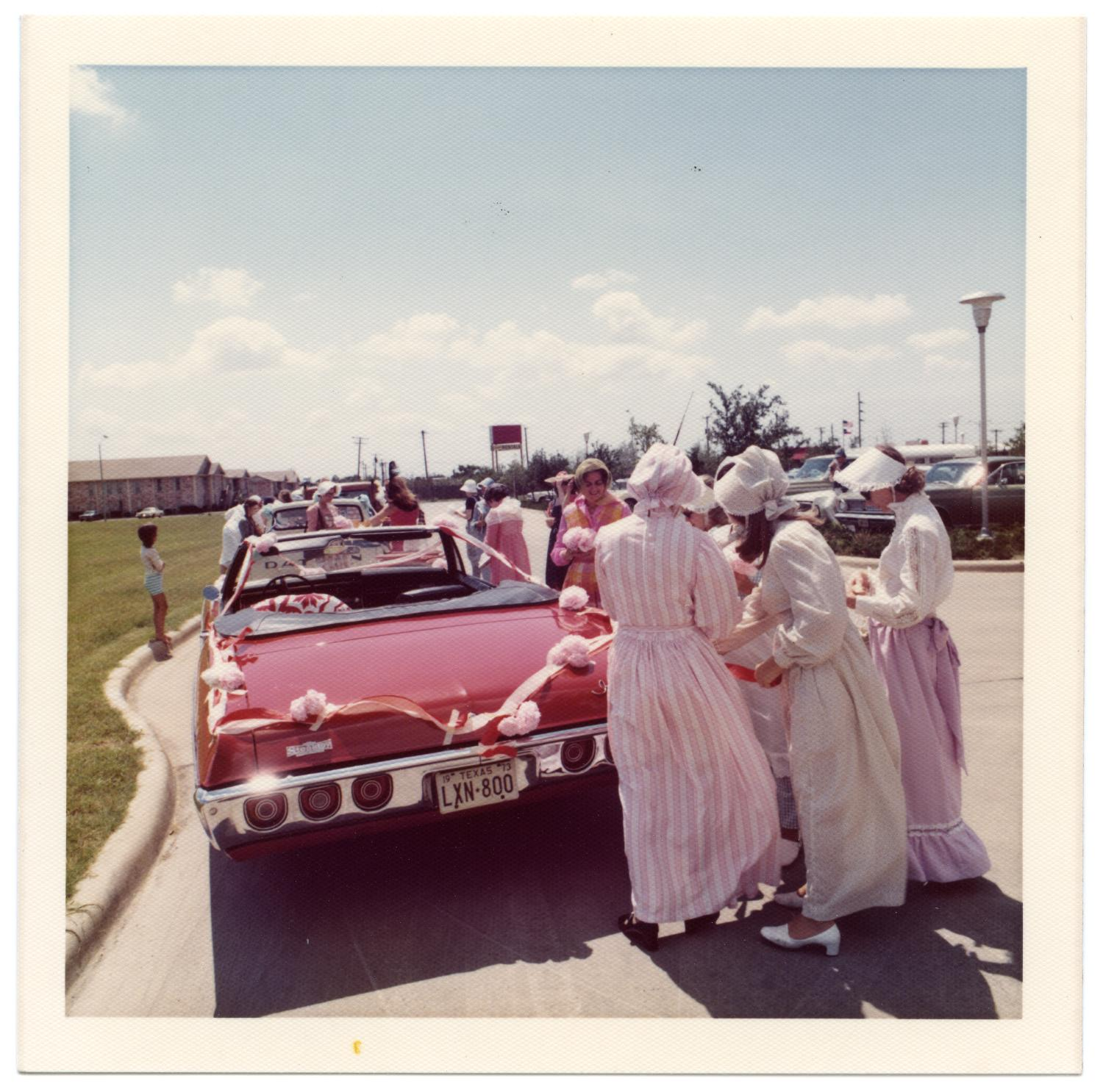 Richardson Centennial Parade, Photograph of a group of women dressed in nineteenth-century costume, waiting to participate in the Centennial parade. They are standing in front of a red convertible car decorated with pink flowers and streamers. In the background, there are other cars and people.,