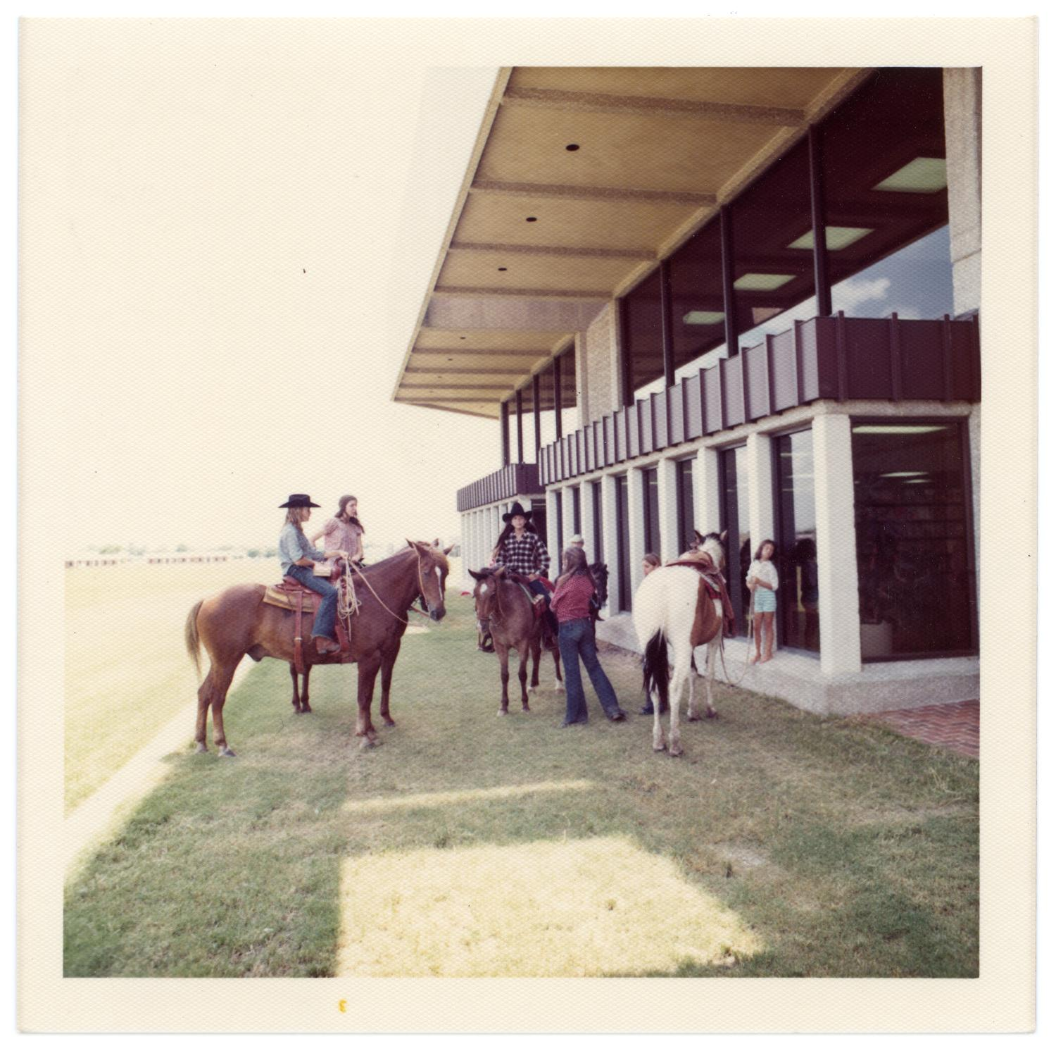 Richardson Centennial Celebration, Photograph of a group of women and horses participating in the Centennial celebration. Three women are riding horses, and are dressed in western wear. The group is standing outside of Richardson Public Library.,