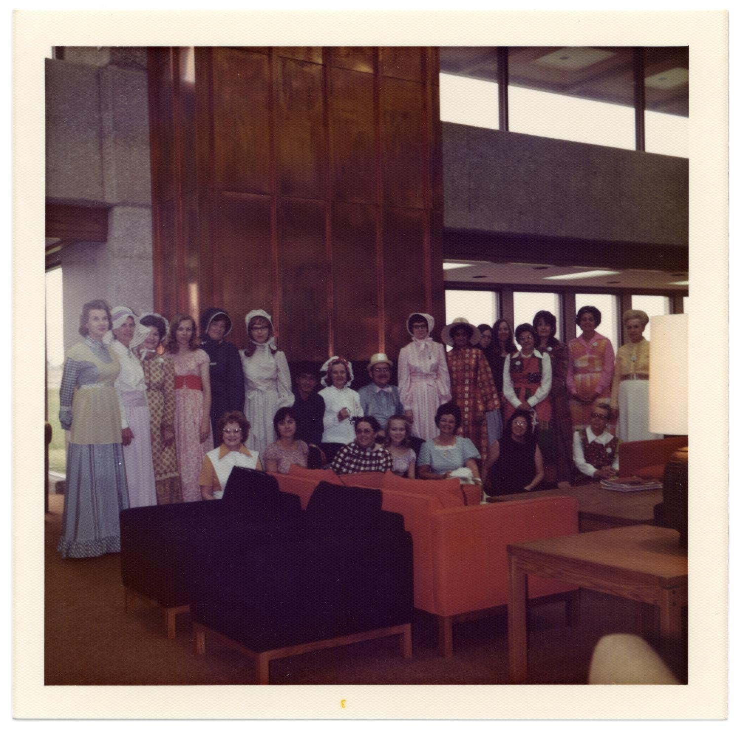Richardson Centennial Celebration, Photograph of a group of men and women, some dressed in nineteenth-century costume, participating in the Centennial celebration. In front of them, there is a set of furniture. The photograph was taken on the first floor of Richardson Public Library.,