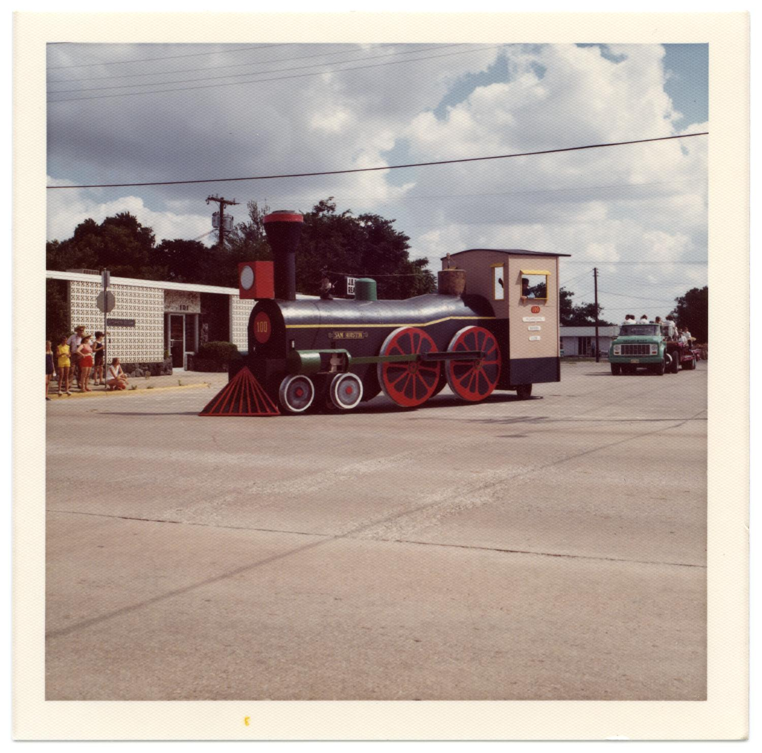 Richardson Centennial Parade, Photograph of a parade float at the Centennial celebration on the corner of Main Street and Greenville Avenue. The float is shaped like a train locomotive. In the background, there are people watching the parade on the left, and a green truck on the right.,