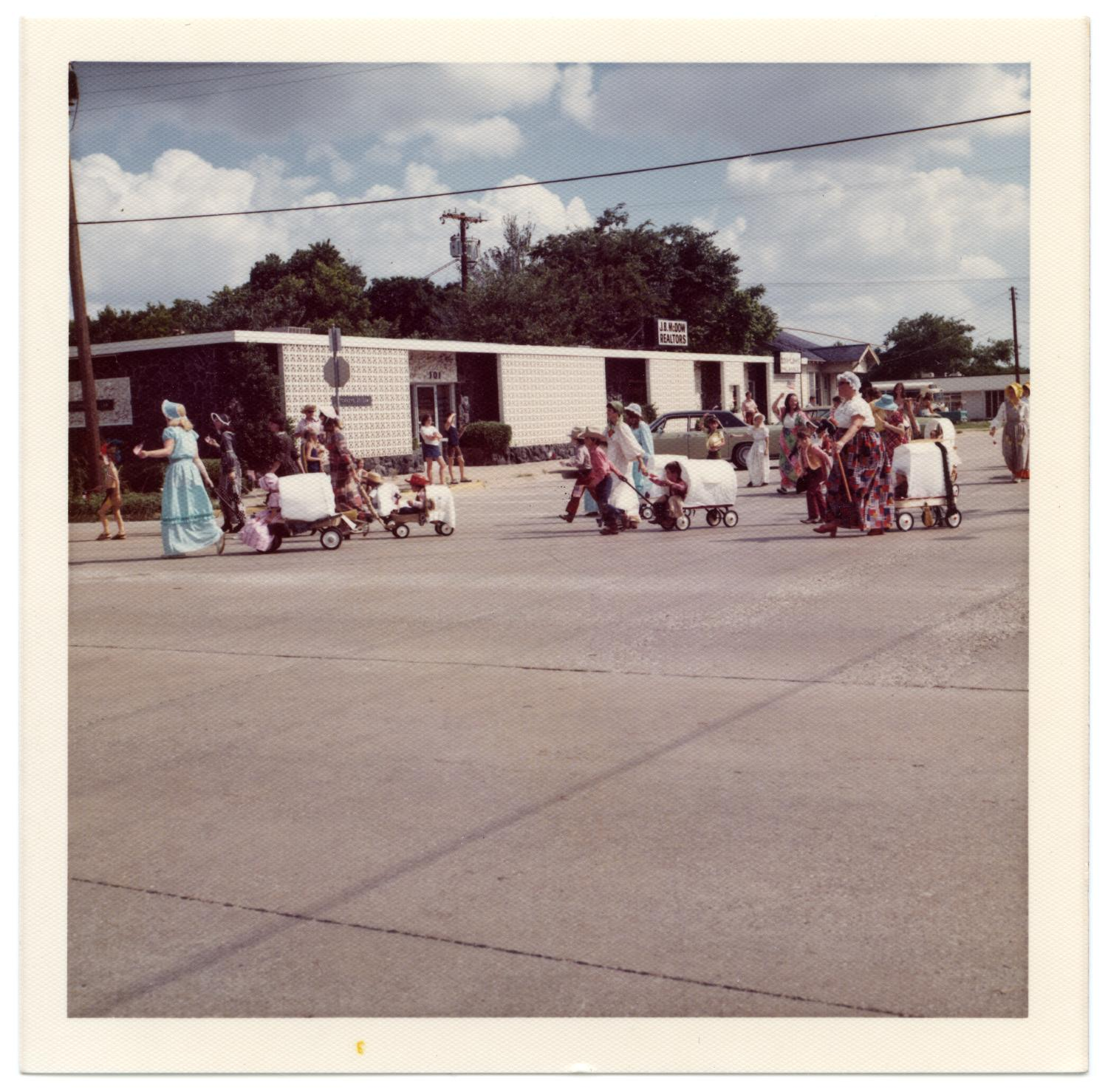 Richardson Centennial Parade, Photograph of a group of people wearing nineteenth-century costumes participating in the Centennial parade on the corner of Main Street and Greenville Avenue. They are pulling toy covered wagons with children riding in them. In the background, there is a building.,