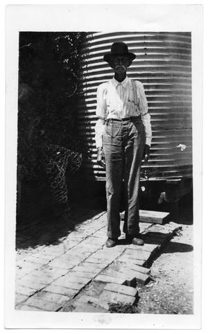 Primary view of object titled '[Portrait of a man standing on a brick walkway]'.