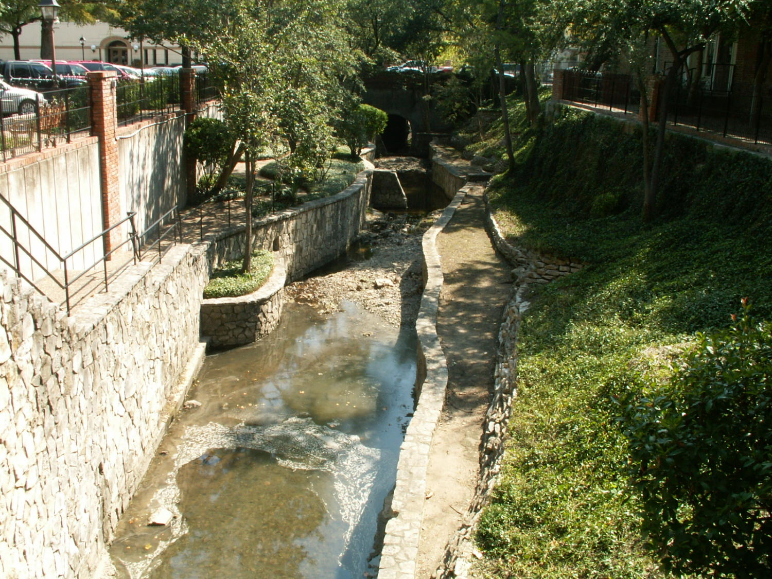 [Small Creek], Photograph of a small creek filled with dirty water in between two stone walls by a parking lot. Cars are visible to the left.,