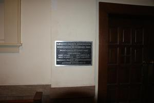 Primary view of object titled '[Plaque Next to Wooden Doors]'.