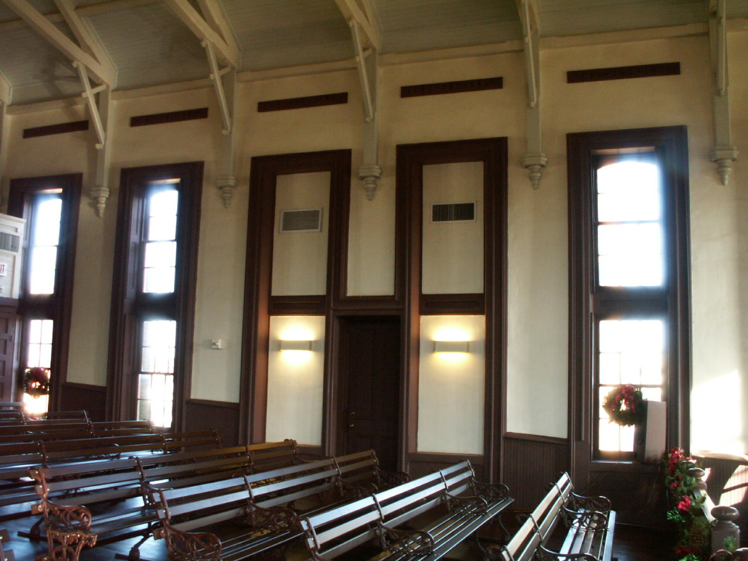 [Rows of Benches], Photograph of several rows of wooden benches in a courtroom in Center, Texas. There are wreaths placed in two of the three windows, and a garland is draped on the railing to the right.,