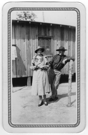 Primary view of object titled '[Woman and man pose outside a building in a Texas Civilian Conservation Corp camp]'.