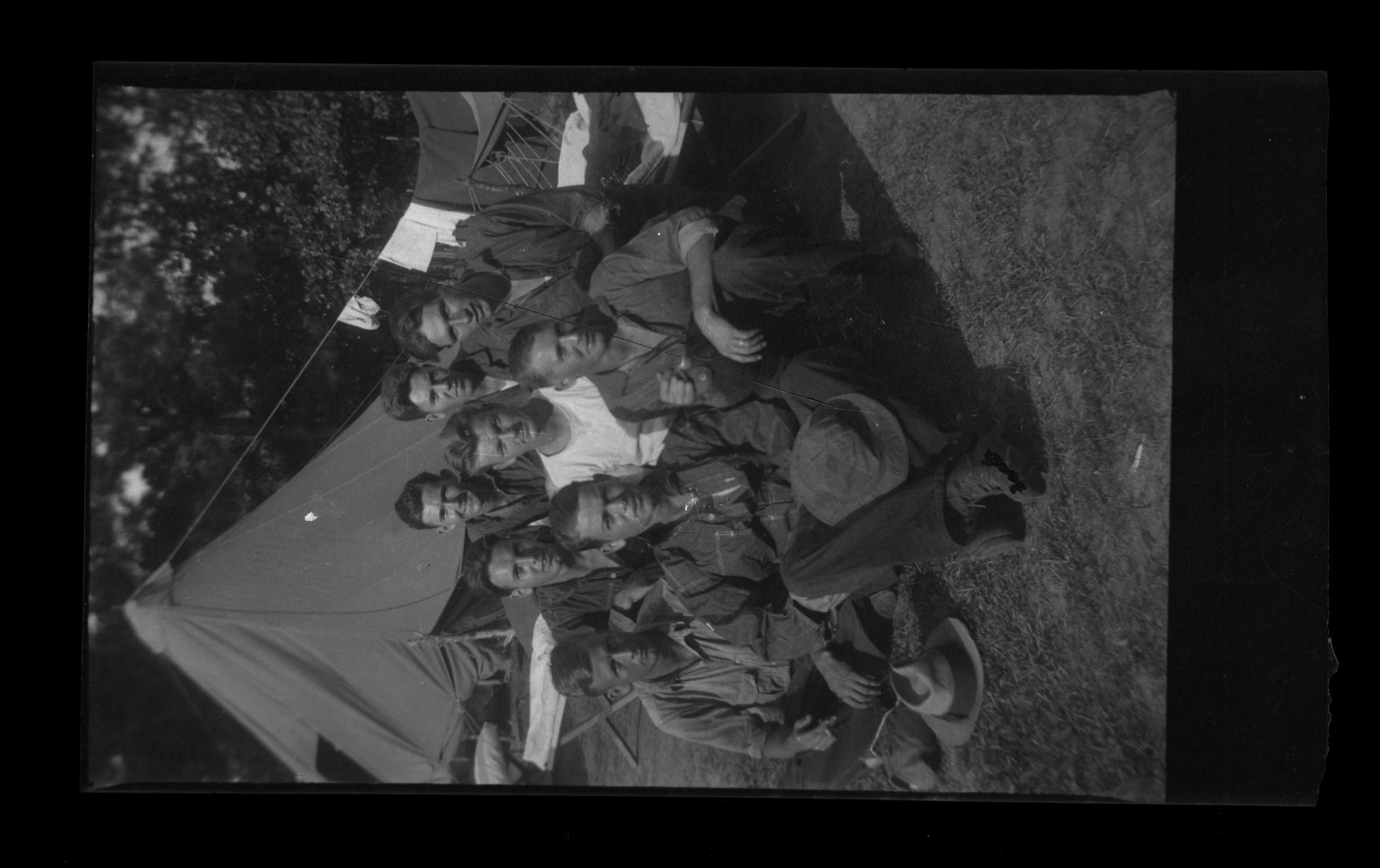 [McCann poses with CCC Camp members in front of tent]                                                                                                      [Sequence #]: 1 of 1