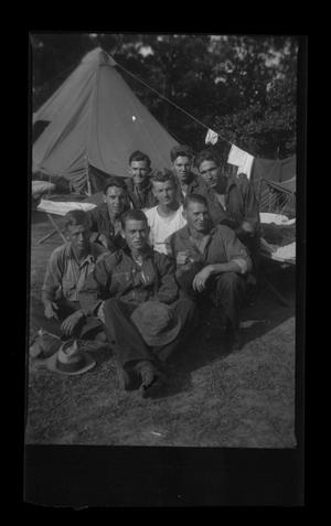 [McCann poses with CCC Camp members in front of tent]
