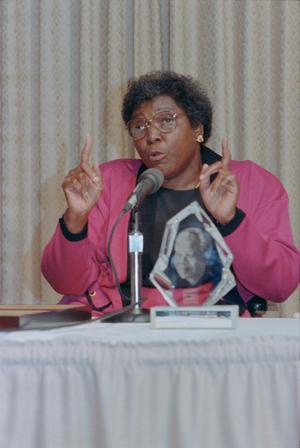 [Barbara Jordan Sitting and Speaking at a Table]