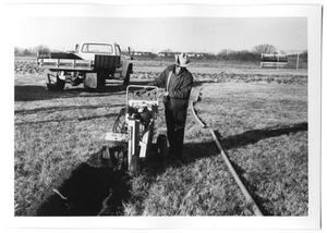 Primary view of object titled '[A Parks Department Employee Operating a Trench Digger]'.