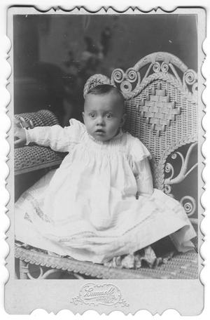 [Unidentifed baby in white dress sits in wicker chair]