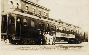 "[Six men in front of a ""Enfield Special"" railroad car at the Southern Pacific station in Austin, Texas]"