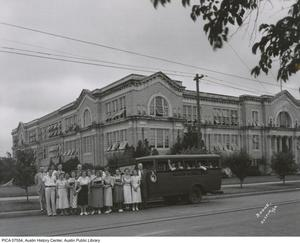 Primary view of [Austin School Bus with group of students and teachers in front of Austin High School, Austin, Texas]
