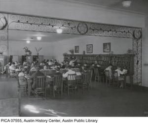 Primary view of [Austin High School students read at long tables in the school library, Austin, Texas]