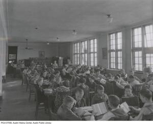 Primary view of [Library interior of Austin High School with students reading at tables, Austin, Texas]