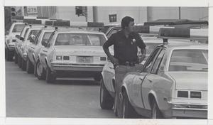 Primary view of object titled '[Sheriff Standing Beside Row of Cars]'.