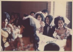 Primary view of object titled '[Bridesmaids, groomsman, and other wedding guests seated at wedding reception at the San Jose Community Center in the Montopolis neighborhood]'.