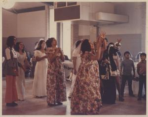 [Bouquet toss with bridesmaids and female guests at a wedding at the San Jose Community Center in the Montopolis neighborhood]