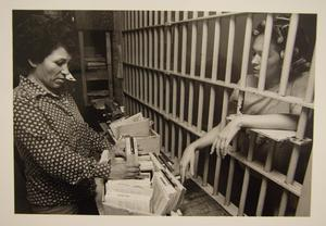 [Female Travis County Jail worker offering books to a female inmate]