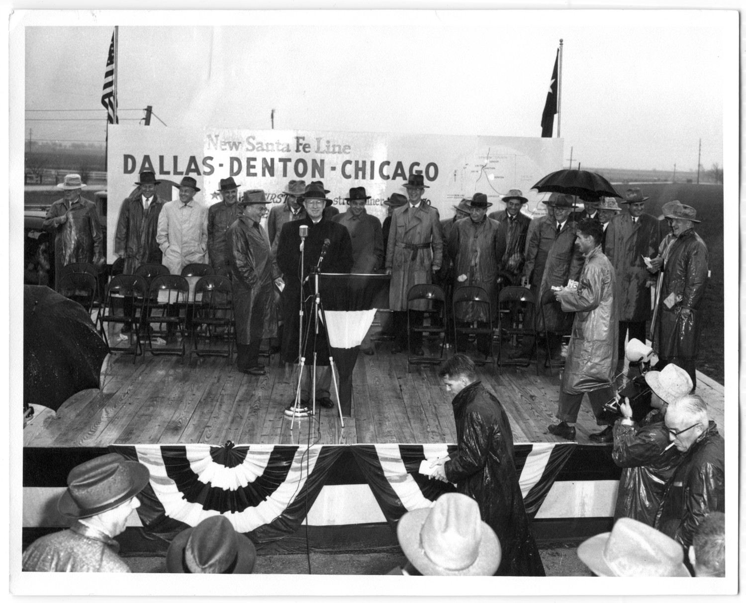 Inauguration of the Santa Fe Railroad Line, Inauguration of the Santa Fe Railroad Line linking Dallas, Denton, and Chicago. It was raining and the photo was taken in north Dallas, near Garland. Among the men heading the groundbreaking ceremony were Railroad president Fred Gurley, Jerome Crossman, president of the Dallas Chamber of Commerce, E. W. Morrison, a Denton businessman who strongly supported the line, Dallas Mayor R. L. Thornton, and Denton Mayor J. L. Yarbrough.,