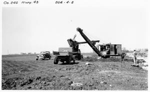 Primary view of object titled '[Loading gravel base on U.S. Highway 79]'.