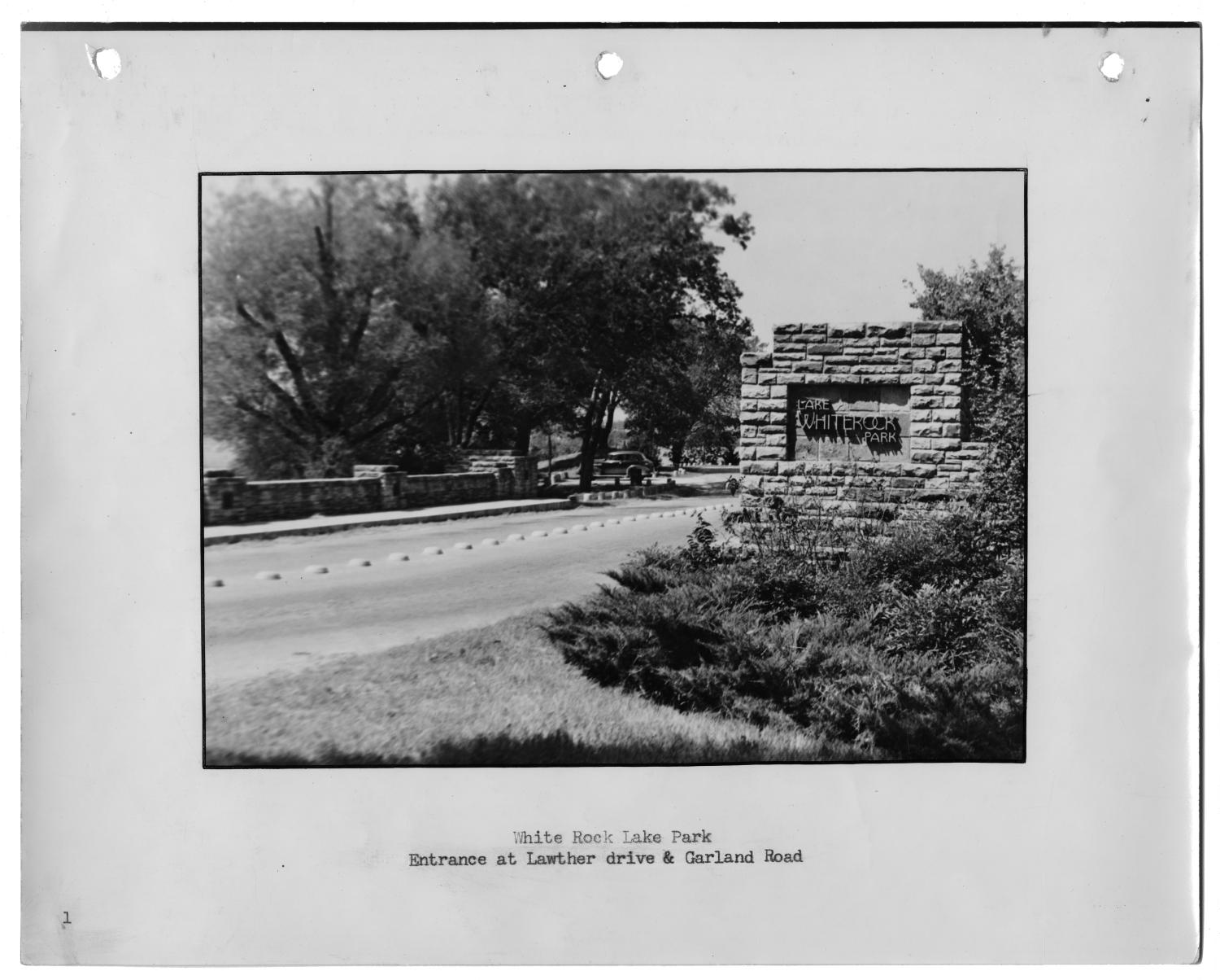 """[Photograph of White Rock Lake Park Garland Road Entrance], Photograph of a driveway leading into White Rock Lake Park. There stone column with the park name on the right side of the drive, in the foreground; theres a small stone wall lining the opposite side of the drive. There are bushes in front of the sign and trees visible in the background. The photograph is attached to a page labeled """"1""""; text under the image says """"White Rock Lake Park, Entrance at Lawther drive & Garland Road."""","""
