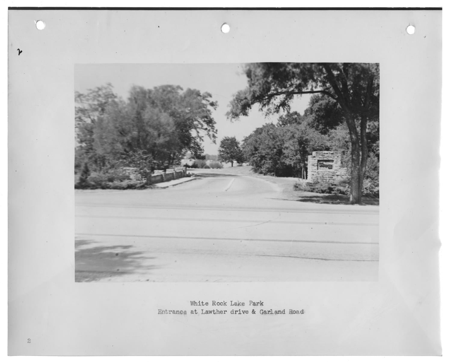 """[Photograph of Entrance to White Rock Lake Park], Photograph of a driveway leading into White Rock Lake Park. There is a small stone wall on the left side of the road and a stone column with the park name on the right side of the drive. There are trees on either side of the road and the lake is partially visible in the background. The photograph is attached to a page labeled """"2""""; text under the image says """"White Rock Lake Park, Entrance at Lawther drive & Garland Road."""","""