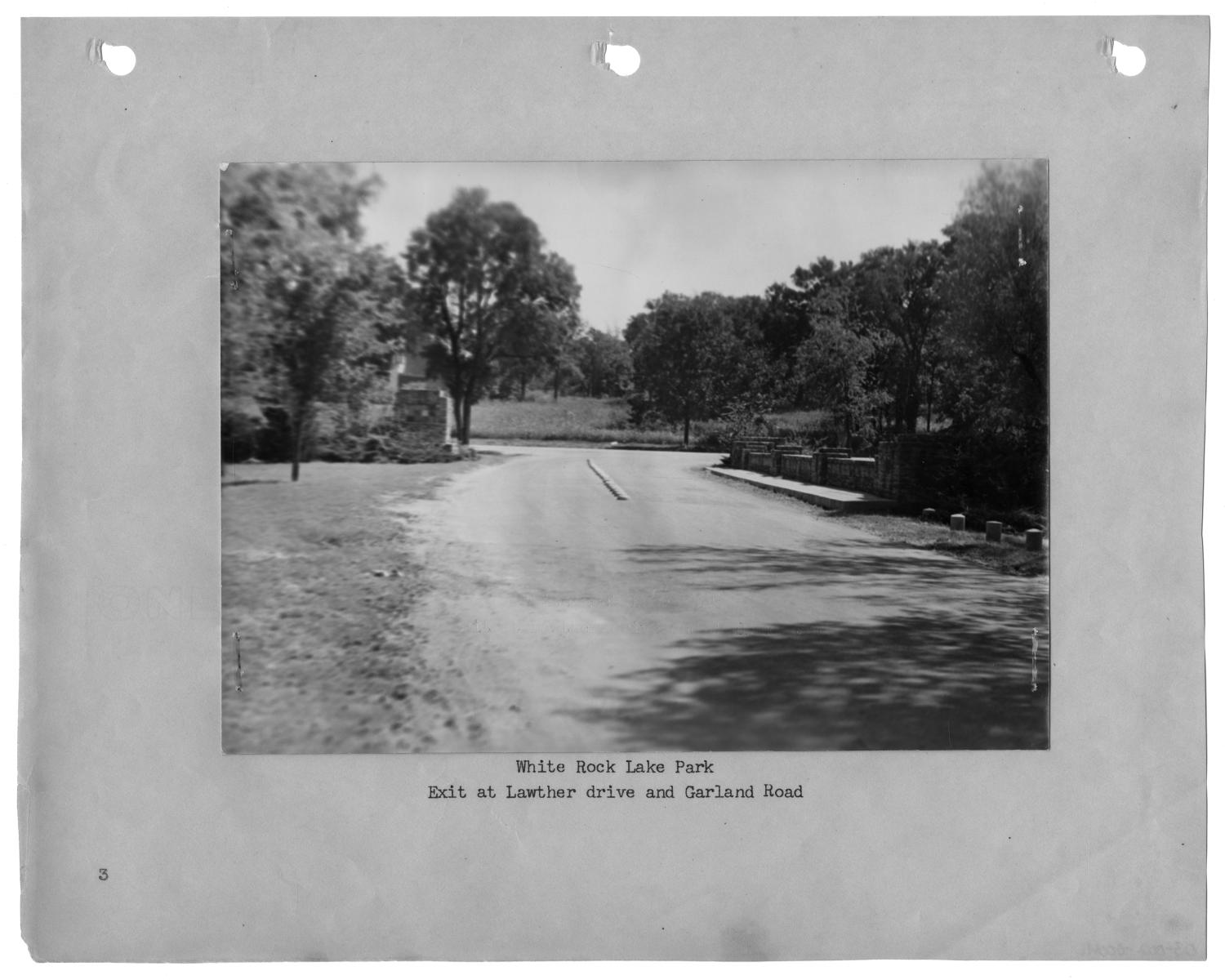"""[Photograph of White Rock Lake Park Exit], Photograph of a driveway leading out of White Rock Lake Park. There is a small stone wall on the right side of the road and a stone column on the left side of the drive. There are trees on either side of the road and Garland Road is visible past the park entrance. The photograph is attached to a page labeled """"3""""; text under the image says """"White Rock Lake Park, Exit at Lawther drive and Garland Road."""","""