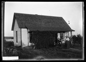 Primary view of object titled '[Two People by House]'.