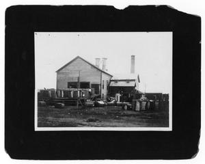 Primary view of object titled '[Bales of Hay in Front of Building]'.