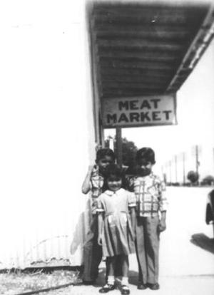 "Primary view of object titled '[Photograph of three children standing by a ""Meat Market"" sign]'."
