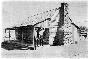 Primary view of object titled 'Torian Log Cabin with Two Men on Front Porch'.