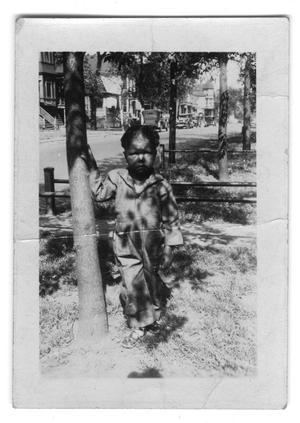 Primary view of object titled '[E. D. Moten, Jr. Standing by a Tree]'.