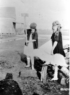 Primary view of object titled 'Alma Hurst Abshire and Wilma Hurst Dobby Chopping Wood in Front of Dickie's Store'.