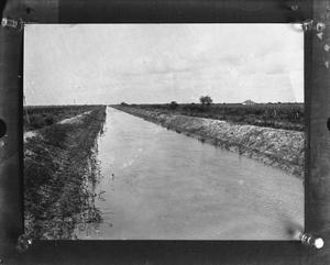 Primary view of object titled '[Photograph of Dirt Canal with Crops and House]'.
